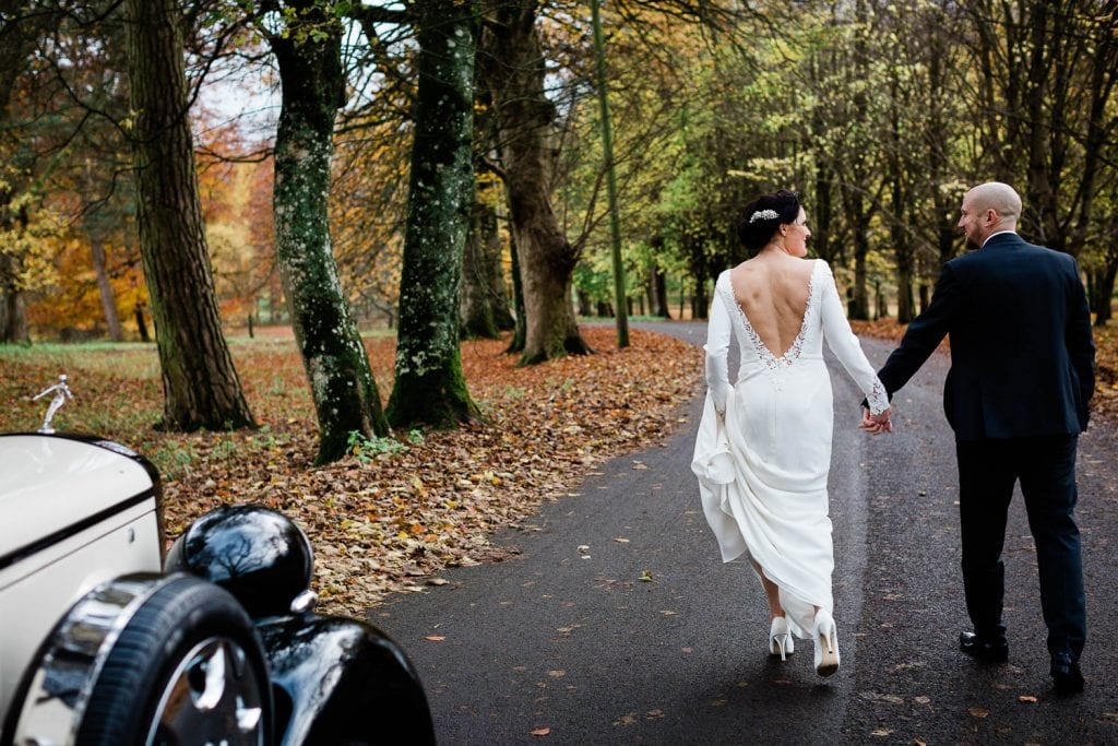 bride and groom holding hands walking away from wedding car teh curragh fallons restaurant kilcullen Kildare